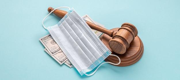 Martelo do juiz com máscara médica e dinheiro sobre fundo azul conceito de corrupção no campo da medicina