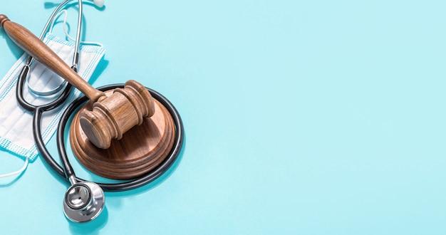 Martelo do juiz com máscara médica e estetoscópio sobre fundo azul proteção do conceito de direitos médicos