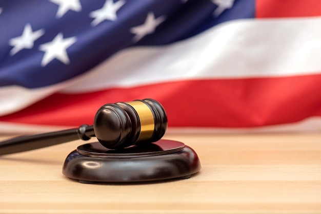 Martelo do juiz de madeira, bandeira dos eua como pano de fundo, imagem conceitual sobre justiça nos eua