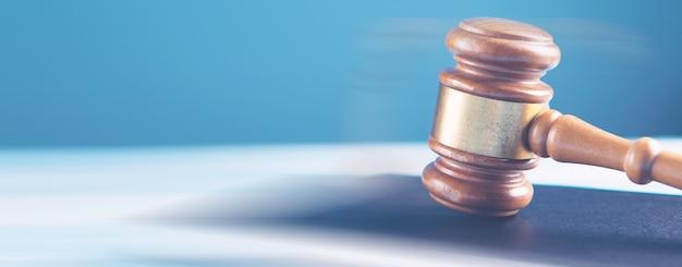 Martelo do juiz de madeira e livros jurídicos.