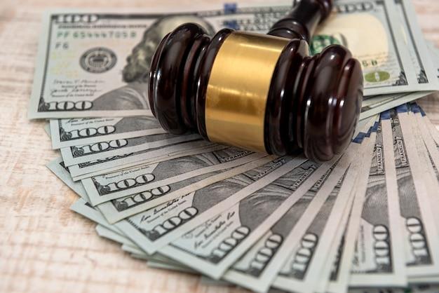 Martelo do juiz de madeira e notas de dólar de dinheiro nos eua conceito de suborno