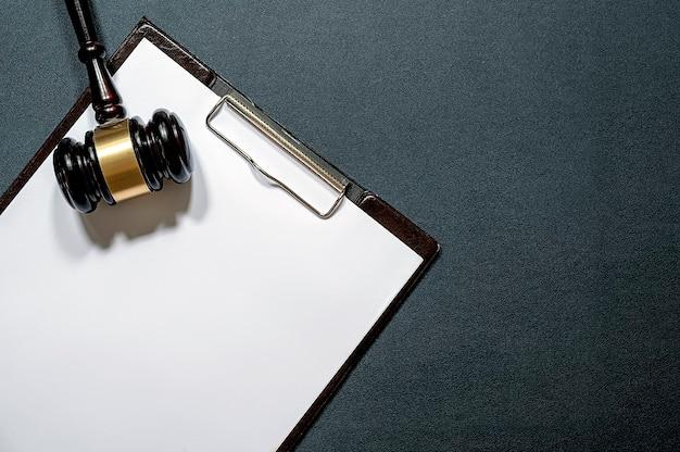 Martelo do juiz de madeira e prancheta de papel em fundo de couro preto.
