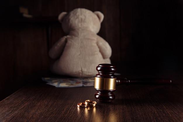 Martelo do juiz de madeira para pagamento de pensão alimentícia notas de dólar com anéis e ursinho de pelúcia