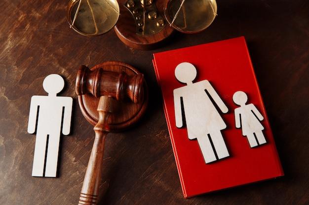 Martelo do juiz divide figuras de madeira da família direito da família e conceito de divórcio