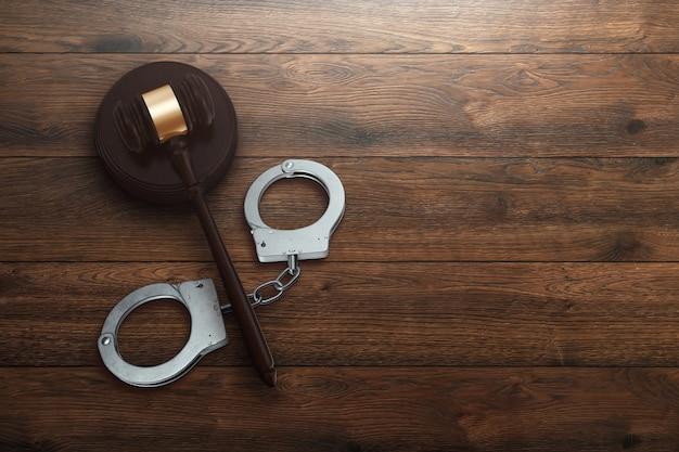Martelo do juiz e algemas em fundo de madeira