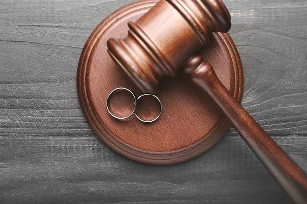 Martelo do juiz e anéis em fundo de madeira. conceito de divórcio