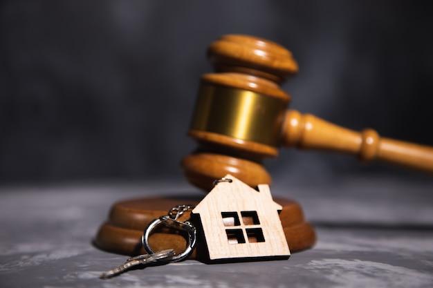 Martelo do juiz e chave da casa em fundo cinza. conceito de direito imobiliário