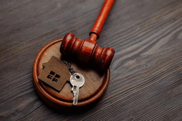Martelo do juiz e chaveiro em forma de duas partes divididas da casa em madeira