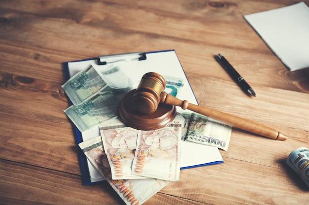 Martelo do juiz e dinheiro na mesa de madeira marrom