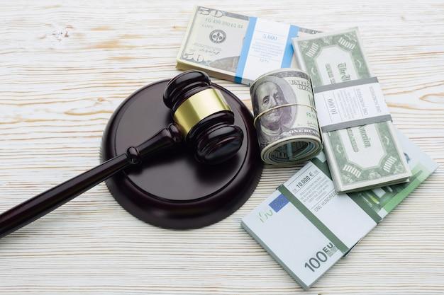Martelo do juiz e maços de dólares e notas de euro em uma mesa de madeira branca