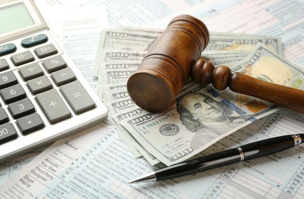Martelo do juiz e notas de dólar no fundo do formulário de imposto de renda