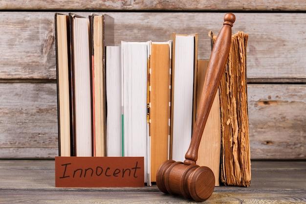 Martelo do juiz e veredicto inocente. muitos livros de lei antigos.