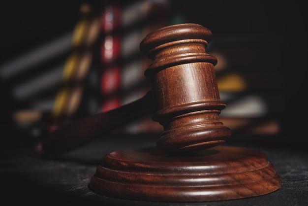 Martelo do juiz (leilão) na mesa contra os livros