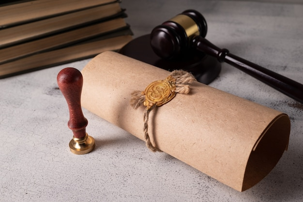 Martelo do juiz, livros, rolo de pergaminho com selo e carimbo em uma velha mesa de madeira