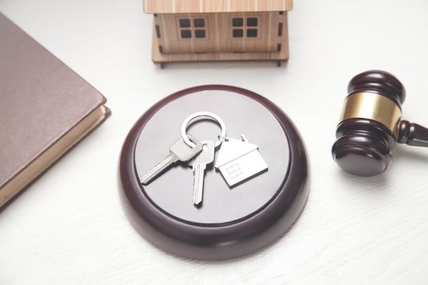 Martelo do juiz, modelo da casa, chaves e livro.