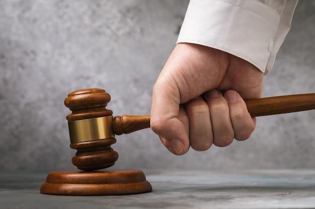 Martelo do juiz na mão contra a parede cinza