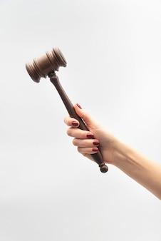 Martelo do juiz na mão feminina no fundo branco. conceito de juiz de mulher. quadro vertical.
