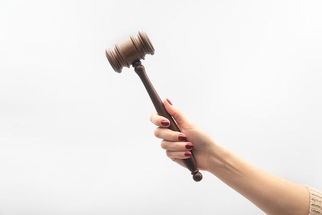 Martelo do juiz na mão feminina no fundo branco. conceito de juiz de mulher.