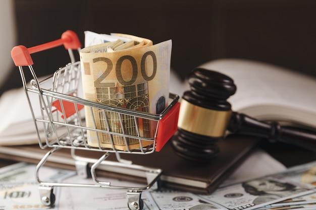 Martelo do juiz ou leilão e cesta de notas de euro em fundo preto