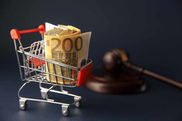 Martelo do juiz, um carrinho de supermercado em um fundo de madeira. defesa dos direitos do consumidor.