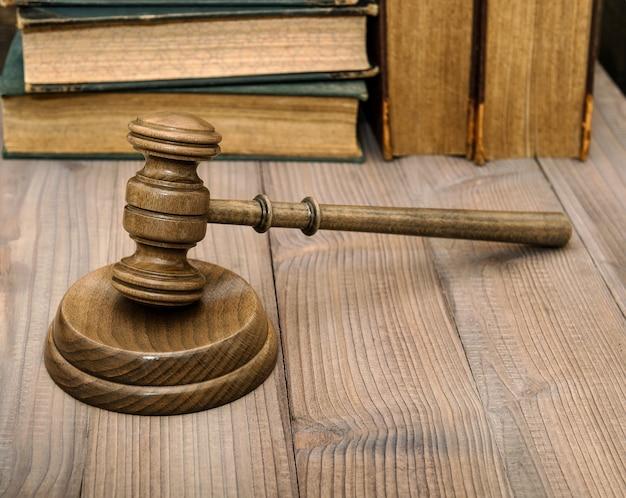 Martelo dos juízes com tampo e livros antigos. martelo de leiloeiro