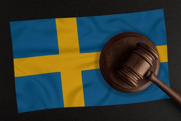Martelo dos juízes e a bandeira da suécia. lei e justiça. lei constitucional.