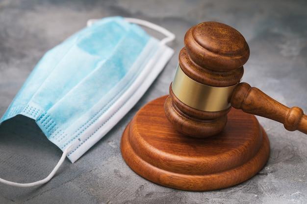 Martelo dos juízes e máscara médica na mesa aproximam o conceito de punição por violar o regime de quarentena