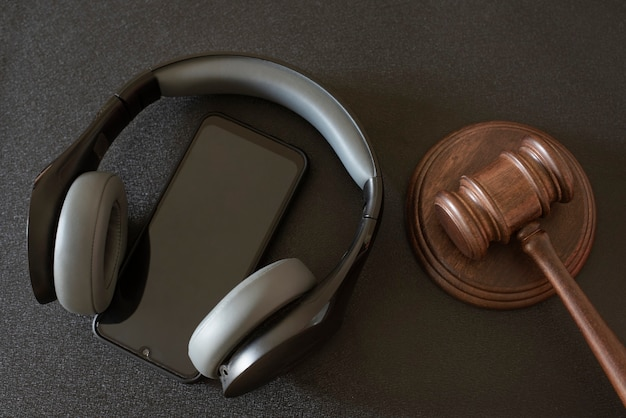 Martelo dos juízes, smartphone e fones de ouvido na superfície preta