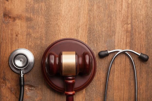 Martelo e estetoscópio no fundo de madeira, foto do símbolo para falhas e erro médico