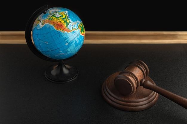 Martelo e globo de madeira do juiz. direito internacional do meio ambiente. conceito de tribunal de justiça e lei.