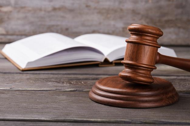 Martelo e livro de direito aberto. plano de fundo cinza da mesa.