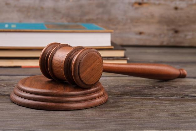 Martelo e livros do juiz. martelo de madeira e livros jurídicos.