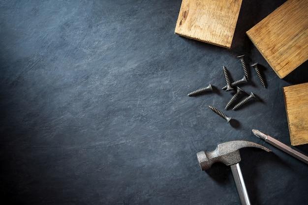 Martelo e madeira serrada em fundo preto de cimento