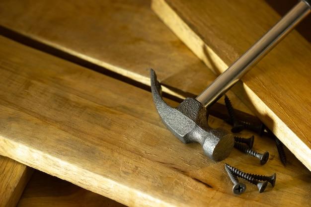 Martelo e parafuso na madeira serrada na iluminação e sombra do sol na manhã. o conceito de artesanato em madeira ou carpintaria.
