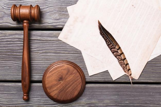 Martelo e pena de madeira de assentamento plano. acessórios de teste de vista superior com papéis.
