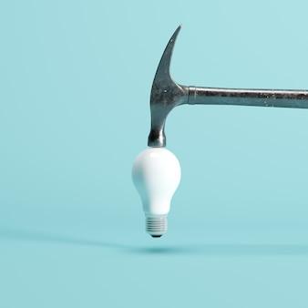 Martelo está batendo em branco lâmpada estouro com fundo azul