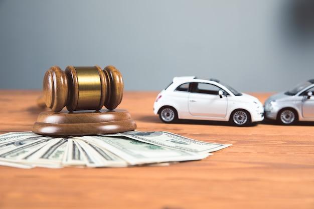 Martelo judicial com dinheiro e carro em uma mesa de madeira