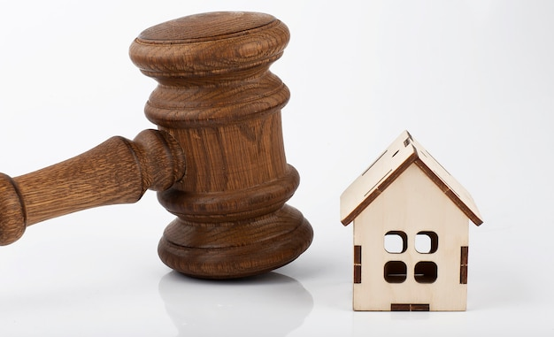 Martelo marrom e modelo de casa de madeira