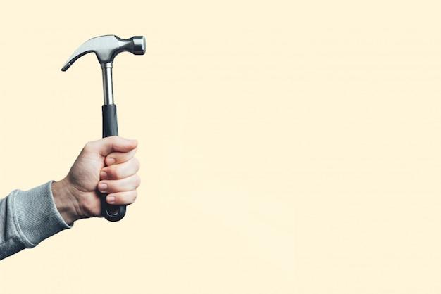 Martelo na mão isolado. homem segurando um martelo vintage, ferramenta na mão.