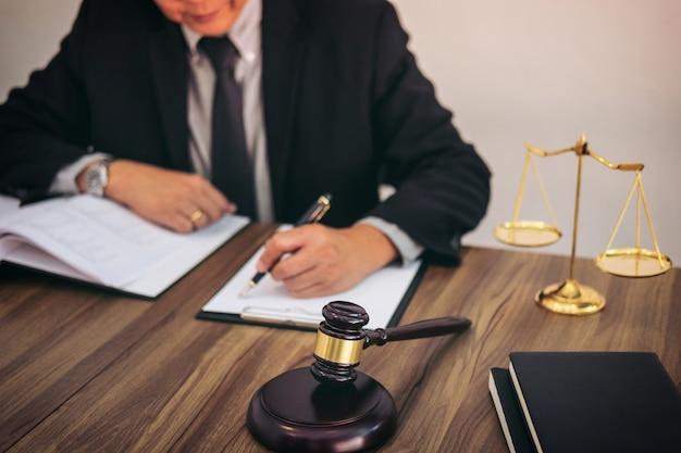 Martelo na mesa de madeira e advogado ou juiz trabalhando com acordo na sala de audiências