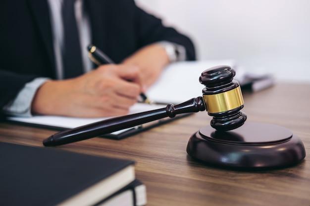 Martelo na mesa de madeira e advogado ou juiz trabalhando com acordo