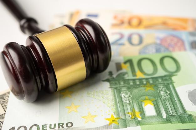 Martelo para advogado do juiz sobre fundo de notas de euro.