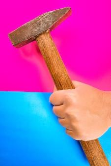 Martelo para reparo na mão em um espaço colorido ou rosa e azul. conceito de reparo ou ferramentas