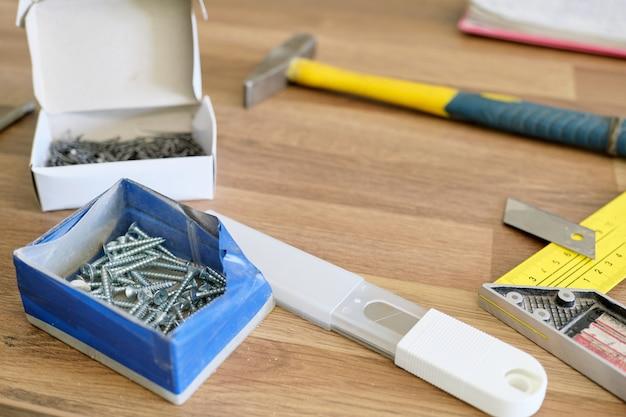 Martelo, pregos, faca de papelaria com lâmina, parafusos para montagem de móveis