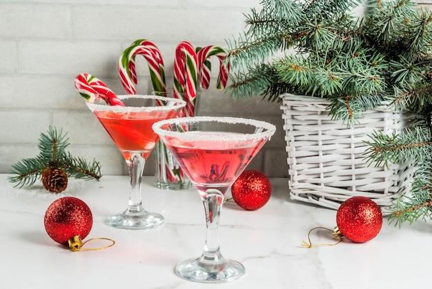 Martini de bebidas de natal, cocktail de hortelã-pimenta rosa com decoração de natal e doce de cana na mesa da cozinha de mármore branco, copie o espaço