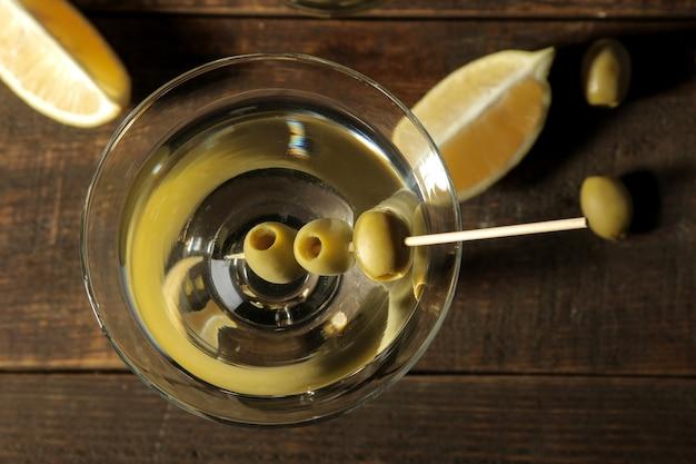 Martini em um copo de vinho com azeitonas verdes no espeto sobre uma mesa de madeira marrom. coquetéis. barra