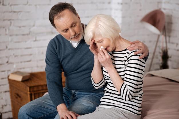 Más notícias. a senhora idosa está chorando sentada perto do marido, que lhe dá apoio.