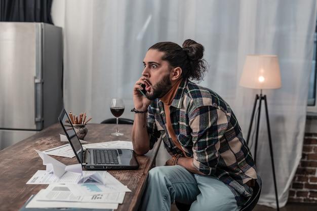 Más notícias. jovem emocional sentado em frente ao laptop enquanto conversa por telefone