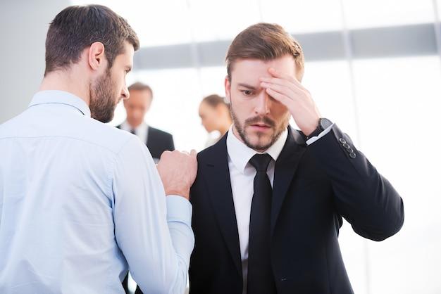 Más notícias. vista traseira do jovem empresário consolando seu colega deprimido e segurando a mão em seu ombro com pessoas em pé ao fundo