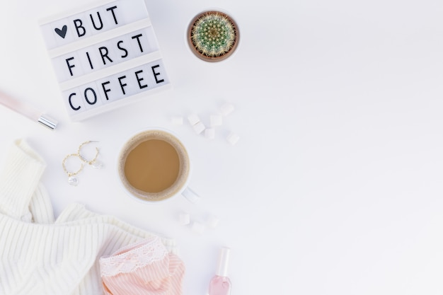 Mas primeiro texto de café na mesa de luz com a xícara de café e fundo branco